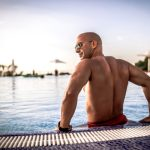 Man Sitting By Pool With Increased Drive and Energy Thanks to Testosterone Replacement Therapy